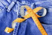Fita métrica contra o pano de fundo das calças de brim — Foto Stock