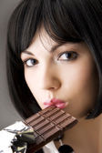 Sexy brunette, who eats chocolate — Stock Photo