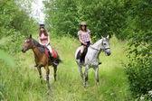女の子は公園で馬に乗る — ストック写真