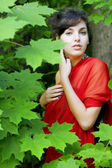Girl in the red in the green leaves — Stock Photo