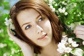 Beautiful girl among the blooming trees — Stock Photo