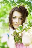 Beautiful girl among the blooming trees — Stock Photo