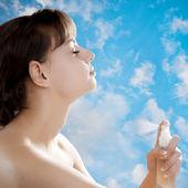 Girl smelling perfume — Stock Photo