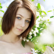 Stock Photo: Girl on a background of flowering flowers