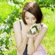 Girl on a background of flowering flowers — Stock Photo