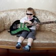 Little boy fashion guitarist sitting on the glamorous couch — Stock Photo