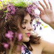 Girl wearing a wreath of wild flowers in the field — Stock Photo #7532862