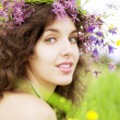 Girl wearing wreath of wild flowers in field — стоковое фото #7532874