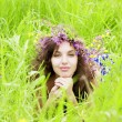 Girl wearing a wreath of wild flowers in the field — Stock Photo