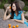 Beautiful young girl with the mandarins in nature — Stock Photo