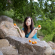 Stock Photo: Beautiful young girl with mandarins in nature