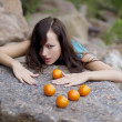 Foto Stock: Beautiful young girl with mandarins in nature