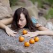 Beautiful young girl with mandarins in nature — Stockfoto #7533182