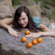 Beautiful young girl with the mandarins in nature — Stockfoto