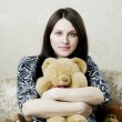 Pregnant woman sitting on a vintage couch with toys — Stock Photo
