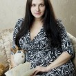 Pregnant woman who reads book sitting on the sofa — Стоковая фотография