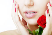 Beautiful girl face close up with a rose in hand — Stock Photo