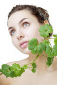 Beautiful young woman with a green plant — Stock Photo