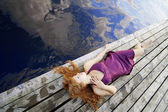 Beautiful red-haired girl on the pier in a purple dress — Stock Photo