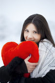 Beautiful girl in winter forest with red heart — Stock Photo