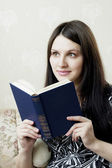 Woman, who reads book sitting on the sofa — Stock Photo