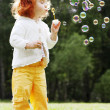 Stock Photo: Girl puts bubbles in park