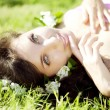 Beautiful girl lying on the grass with flowers - Foto Stock