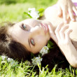 Beautiful girl lying on the grass with flowers — Stock Photo #7615968