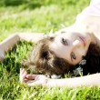 Beautiful girl lying on the grass with flowers - Stok fotoğraf