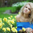 Beautiful positive girl in a park, surrounded by flowers — Stock Photo #7616107