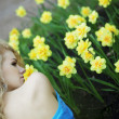 Beautiful positive girl in a park, surrounded by flowers — Stock Photo #7616113