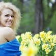 Beautiful positive girl in a park, surrounded by flowers — Stock Photo #7616117