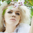 Beautiful positive girl in a park, surrounded by flowers — Stock Photo #7616121