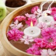 Spa therapy, flowers in water, on a bamboo mat. — Stock Photo