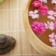 Spa therapy, flowers in water, on a bamboo mat. — Stok fotoğraf