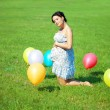 Pregnant woman with balloons on grass — Photo
