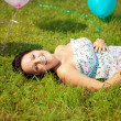 Pregnant woman with balloons on grass — Stock Photo