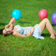 Stock Photo: Pregnant woman with balloons on grass