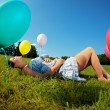 Foto Stock: Pregnant woman with balloons on grass