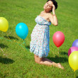 Pregnant woman with balloons on grass — Stock fotografie