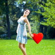 Beautiful pregnant woman with a red heart — Stock Photo