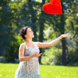 Foto Stock: Beautiful pregnant woman with a red heart