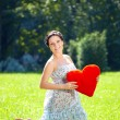 Beautiful pregnant woman with a red heart — Stock Photo #7616570
