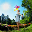 Woman with balloons on grass — Stock Photo #7616581