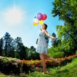 Woman with balloons on grass - Stock Photo