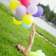 Woman holding bunch of colorful air balloons — Stock Photo