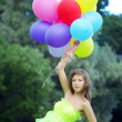 Stock Photo: Womholding bunch of colorful air balloons