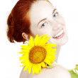 Beautiful smiling girl with a sunflower in the hands — Stock Photo #7616785