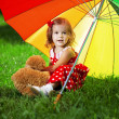 Little girl with rainbow umbrellin park — Stock Photo #7616887