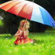 Little girl with rainbow umbrellin park — Stockfoto #7616890